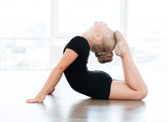 Beautiful graceful little girl dancing and stretching in ballet class
