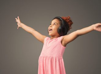 Little black girl dancing in headphones at gray studio background